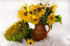 Girasoles amarillos en un florero de cerámica en la tabla de madera con t blanco Foto de archivo