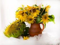 Girasoles amarillos en un florero de cerámica en la tabla de madera con t blanco Fotos de archivo