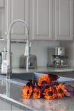 Girasoles anaranjados en un contador de cocina moderno Imágenes de archivo libres de regalías