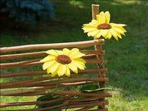 Girasoles artificiales en la cerca decorativa Fotos de archivo