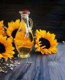 Girasoles, semillas de girasol y una botella de Imagenes de archivo