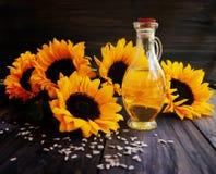 Girasoles, semillas de girasol y una botella de aceite Foto de archivo
