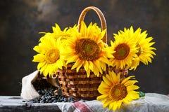 Girassóis bonitos em uma cesta em uma tabela de madeira Fotografia de Stock Royalty Free