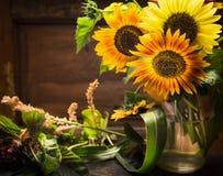 Girassóis no vaso na tabela sobre o fundo de madeira Foto de Stock Royalty Free
