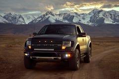 Giri americani opachi neri grandi del rapace del camioncino sulla steppa di Kurai al tramonto Ghiacciai e montagne di Altai nei p immagini stock