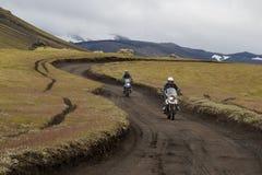 Giri dei motociclisti su una strada non asfaltata fra le montagne e le colline verdi immagine stock libera da diritti
