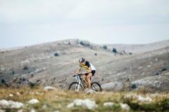 Giri del ciclista in mountain-bike del cavaliere del giovane in montagne fotografia stock