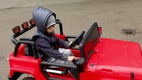 Giri del ragazzo sull'automobile del giocattolo stock footage