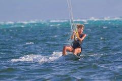 Giri di un aquilone-surfista della giovane donna Immagini Stock