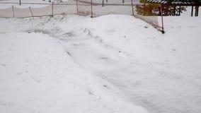 Giri felici della ragazza e snowtube sorridente sulle strade nevose video d archivio