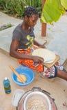 Giriama woman cooking pancakes outdoors Stock Photo