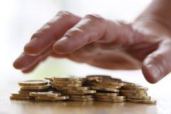 Girig hand som ut griper eller når för högen av guld- mynt För slut begrepp upp - för skatt, bedrägeri och girighet royaltyfri foto
