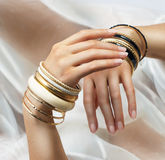 Girl's hands with golden bracelets stock photography