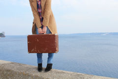 Girl's hands holding an old suitcase standing near the seashore Royalty Free Stock Photography