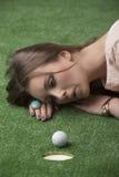 Girl's lying on grass with golf ball Stock Photos