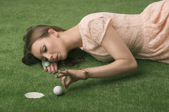 Girl's lying on grass with golf ball Stock Image