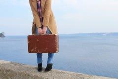 Girl's räcker att rymma ett gammalt resväskaanseende nära kusten Royaltyfri Fotografi