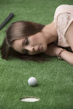 Girlâs lying on the beach na trawie z piłką golfową Zdjęcie Stock