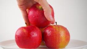 Girl& x27; 采取一个湿红色苹果,轻的背景的s手 免版税库存图片