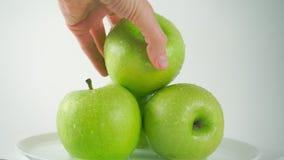 Girl& x27; 采取一个湿绿色苹果,轻的背景的s手 免版税库存照片