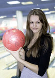 Girl with 10 pin bowling ball. Happy girl with 10 pin bowling ball, alley in background stock images