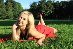 Girl. An attractive blonde woman lying on the grass in the park Stock Photo