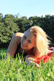Girl. An attractive blonde woman lying on the grass in the park Stock Images
