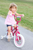 Girl. Smiling little girl cycling  in the park Stock Photo