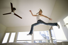 Girl (11-13) Jumping Up And Down On Bed, Mirroring Shape Of Electric Ceiling Fan, Smiling, Portrait, Low Angle View Stock Images