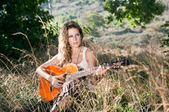 Girl. Bucolic girl with guitar on autumm field Stock Photo
