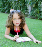 Girl 12 years write in a notebook Royalty Free Stock Photo