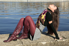 Girl. The beautiful girl sits on river bank Moscow, has cast away a head back Stock Photography
