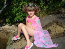 Girl. Summer on a sunny day, five-year old girl in a pink bathing suit rests on a rock near the water Royalty Free Stock Images