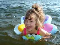 Girl. In the summer the beautiful six-year girl floats on water on a life buoy Stock Photo