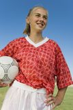 Girl (13-17) in soccer kit holding ball. Portrait, low angle view royalty free stock image