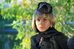 The girl. In black mourning clothes against green foliage looks upwards Stock Photography