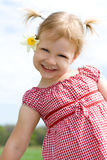 Girl. A vertical picture of a happy three year old girl in pigtails and with a Jonquil flower tucked behind her ear dressed in a red and white checked blouse Stock Images
