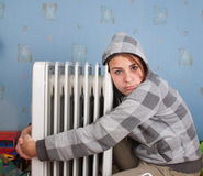 Girl. Young girl is sitting near heater Stock Photo