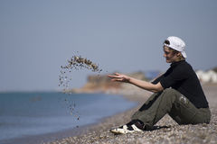 The girl. The young girl sits on a beach and throws stones Royalty Free Stock Photos