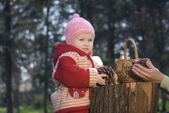 The girl. In a red striped suit plays to wood Royalty Free Stock Photo