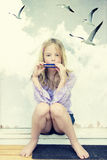 Girl. Little girl playing mouth organ - composite image with added noise Stock Photos