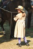 A girl in 1860's period costume tends to horses Stock Photography