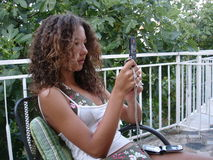 Girl with 2 mobile phones. Teen girl with 2 mobile phones on terrace Stock Photography