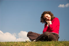 Girl. Pretty girl is sitting and dreaming on sky background royalty free stock image