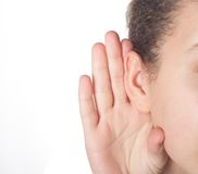 Girl. Listening with her hand on an ear royalty free stock photo
