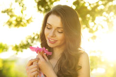 Girl. With flower against spring bokeh background Stock Photo