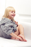 Girl 3 years old in a gray knit sweater. Sitting on a sofa Royalty Free Stock Photo