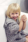 Girl 3 years old in a gray knit sweater. Sitting on a sofa Stock Photo