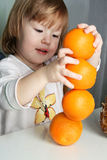 Girl and 4 oranges. Small girl builds figure from 4 oranges Stock Photo