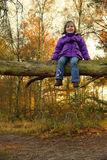Girl (4yr) sitting on a tree Royalty Free Stock Photography